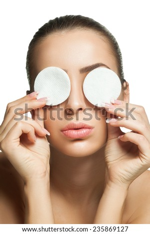 Young girl closes her eyes with cotton discs giving kiss. ?leans healthy skin and removes makeup cotton pad from the face on a white background - stock photo