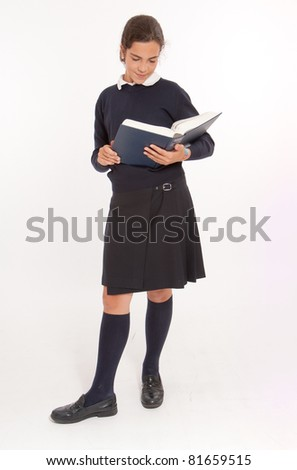 Young girl consulting a big encyclopedia - stock photo