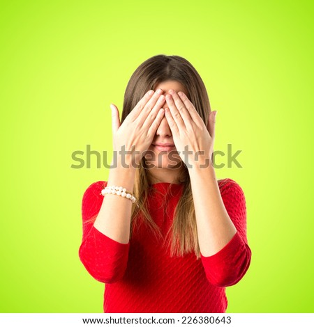 young girl covering her eyes over green background  - stock photo