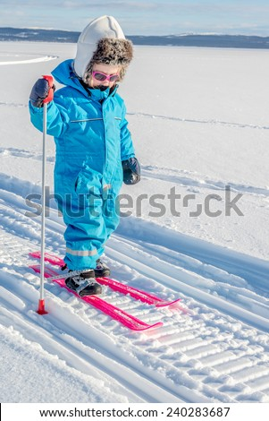Young girl cross-country skiing. In snowmobile tracks. - stock photo