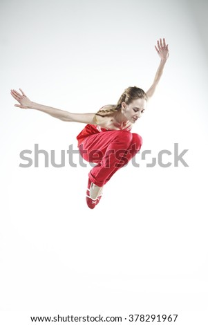 Young girl dancer doing jumps and difficult elements - stock photo