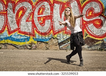 Young girl dancing on graffiti background. Dancing and urban culture concept.   - stock photo
