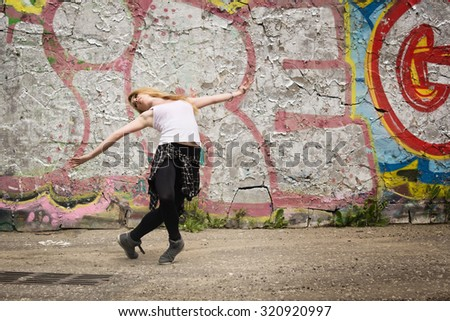 Young girl dancing on graffiti background. Dancing and urban culture concept. Film grain effect  - stock photo