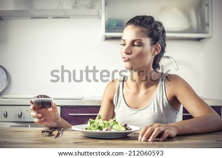 young girl deciding whether to eat healthy food or a sweet - stock photo