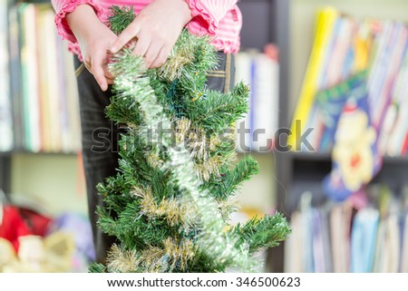 Young girl decorating Christmas tree, close-up - stock photo