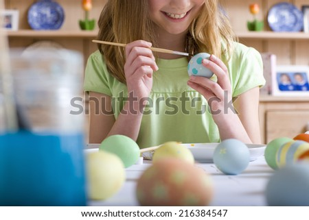 Young girl decorating Easter eggs - stock photo