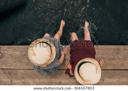 Young girl dipping feet in the lake from the edge of a wooden boat dock - stock photo