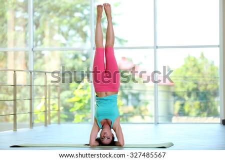 Young girl do complex yoga position in the gym - stock photo
