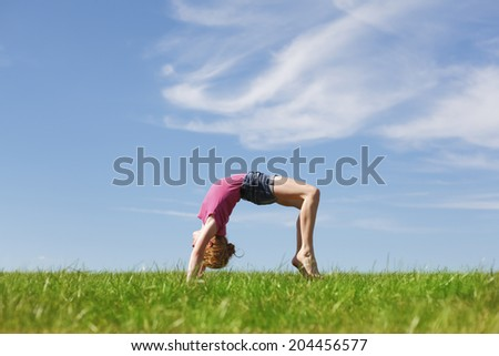 Young girl doing a back arch in a meadow - stock photo