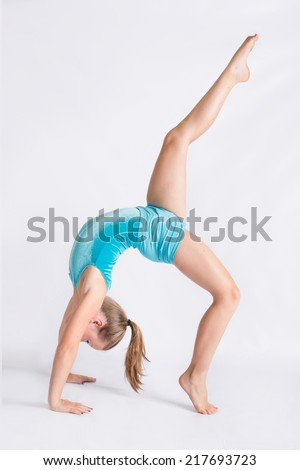 Young girl doing a back bend with one leg held up high - stock photo