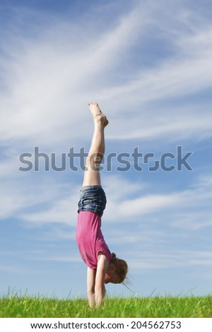 Young girl doing a handstand in a meadow - stock photo
