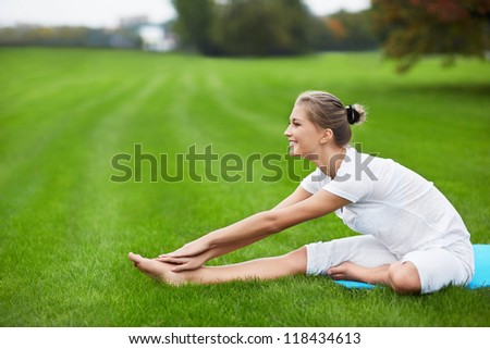 Young girl doing gymnastics in the park - stock photo
