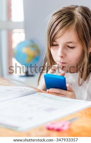 Young girl doing homework and using smartphone - stock photo
