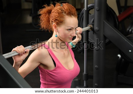 young girl doing squats with barbell - stock photo
