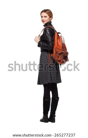 young girl dressed in leather jacket with brown leather backpack on white - stock photo