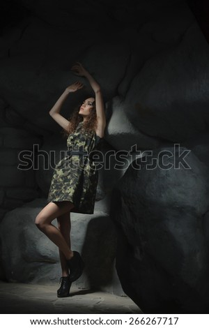 young girl dressed in military clothing, raised his hands up and looks at the light. Not a big ray of hope - stock photo