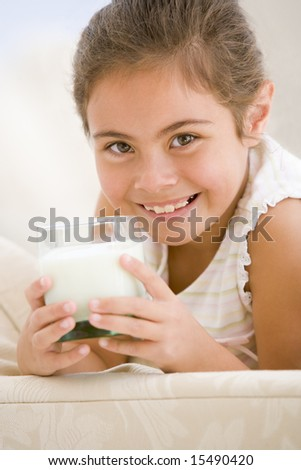 Young girl drinking milk in living room smiling - stock photo