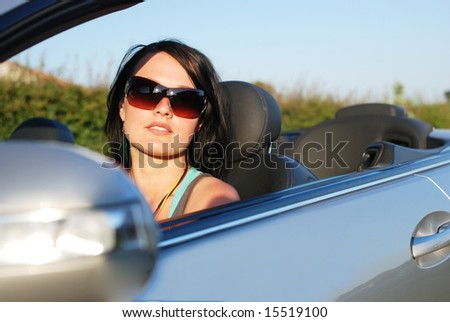 Young girl driving cabriolet car - stock photo