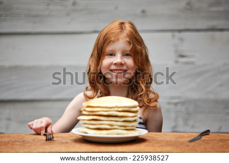 Young girl eating a stack of pancakes.  - stock photo