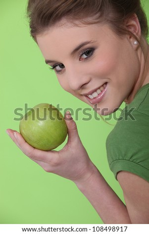 young girl eating apple against green background - stock photo