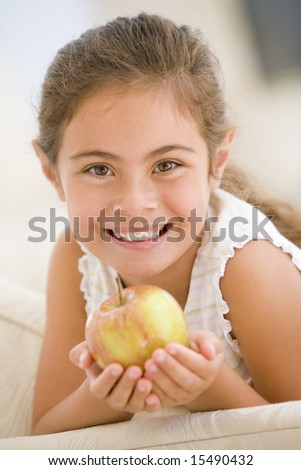 Young girl eating apple in living room smiling - stock photo