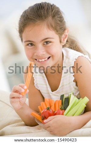 Young girl eating bowl of vegetables in living room smiling - stock photo