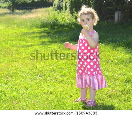 Young girl eating ice cream. Pretty child, toddler, wearing pink and white dress. She has blonde curly hair. Background is green grass.  Bright and colourful. - stock photo