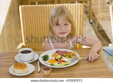 Young girl eating in restaurant - stock photo