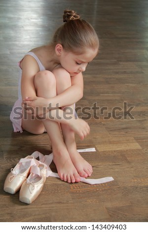 Young girl engaged in a pink ballet tutu and pointes in the ballet hall on the wooden dance floor - stock photo