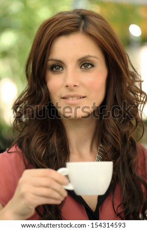 Young girl enjoying a cup of coffee - stock photo