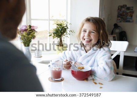 Young girl enjoying breakfast with father - stock photo