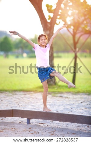Young girl enjoying on balancing activity at the outdoor park in evening sun. - stock photo