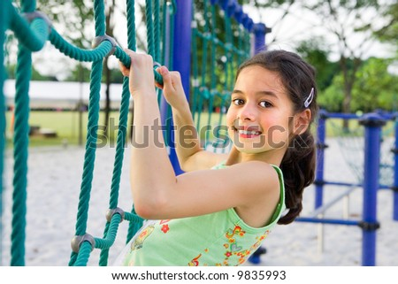 Young girl enjoying the climbing rope activity in the playground - stock photo