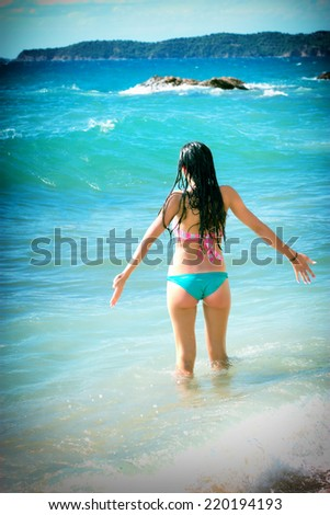 Young girl enjoys on beach in sea waves - stock photo