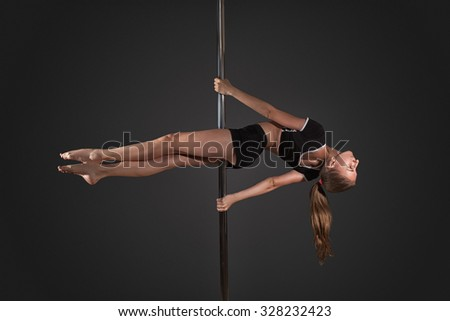 Young girl exercise pole dance before a gray background - stock photo
