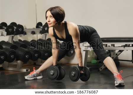 Young girl, exercising with dumbbells in a gym - stock photo