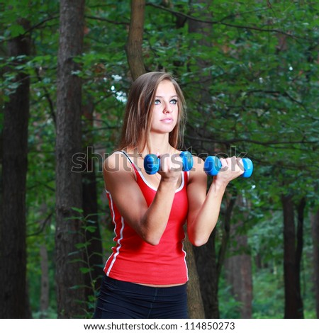 Young girl exercising with dumbbells in the park - stock photo