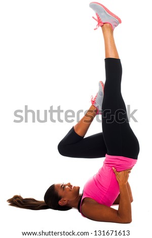Young girl exercising with leg raised up. Isolated over white. - stock photo