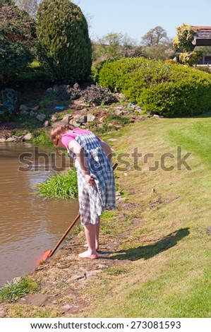 Young girl exploring the garden pond. - stock photo