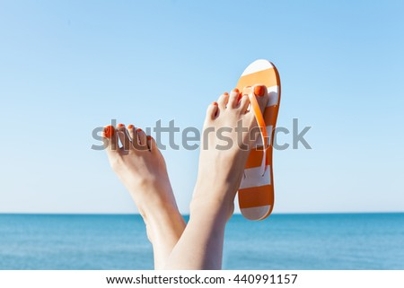Young girl feet in colorful flip-flop sandal on sea beach - stock photo