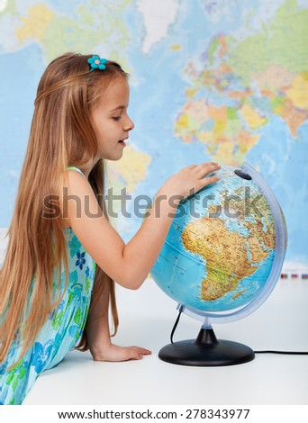 Young girl finding places on a globe - elementary school education concept - stock photo