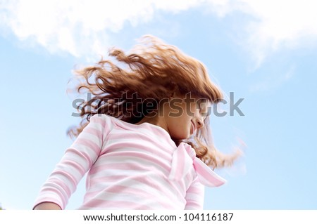 Young girl flicking her hair in the air against a blue sky. - stock photo