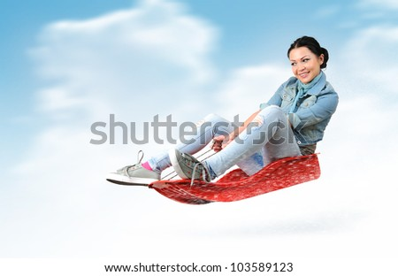 Young girl fly on a sled in the snow, concept winter driving - stock photo