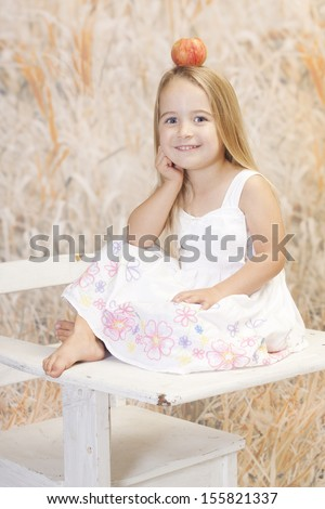 Young girl getting her education in a non traditional way, she is also having a little fun with an apple on her head. - stock photo