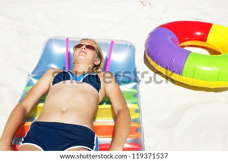Young girl getting some sun at the beach reclining on an air mattress in the sand - stock photo