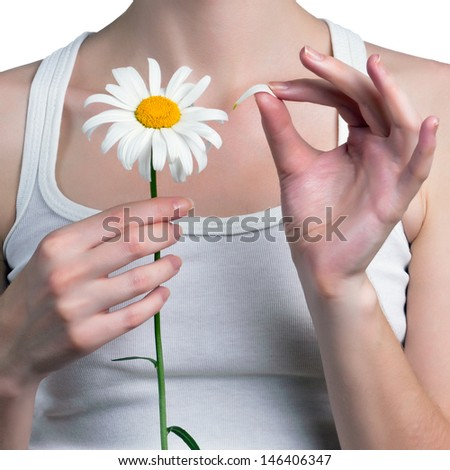Young girl guesses on a chamomile flower. Young girl tears off petals of daisy.  - stock photo