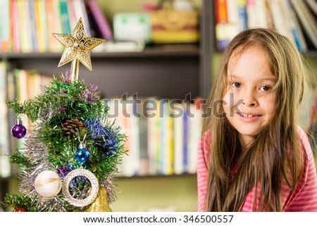 Young girl happily decorating Christmas tree - stock photo
