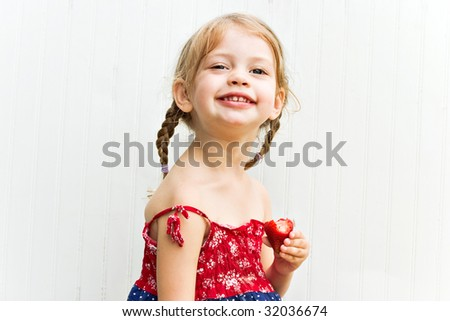Young girl happily eating strawberries - stock photo