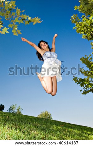young girl happy jumping at the park - stock photo