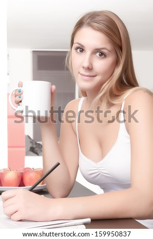 Young girl happy relaxed is drinking a cup of tea and reading a newspaper - stock photo